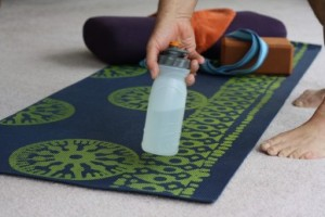Hand placing water bottle on yoga mat.